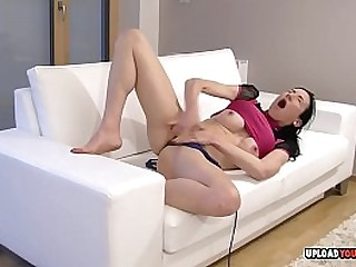 Sexy chick spreads her legs on the white couch to finger her juicy love tunnel.